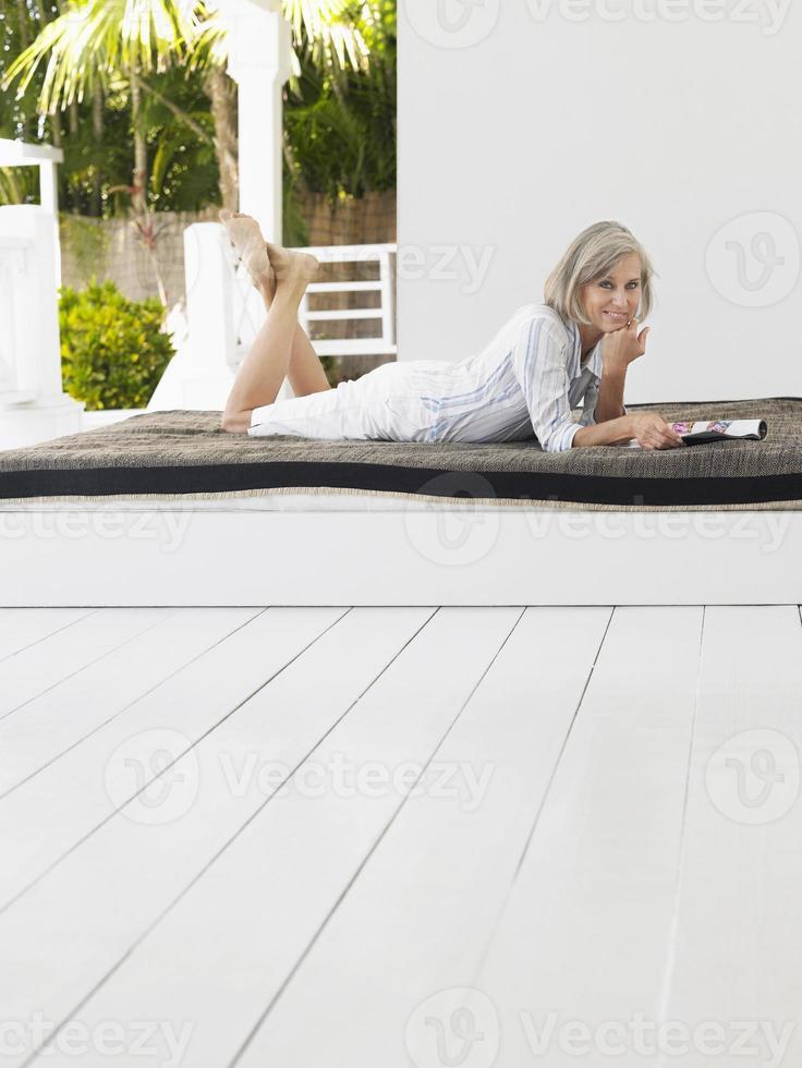 mujer de mediana edad acostada en el sofá cama foto