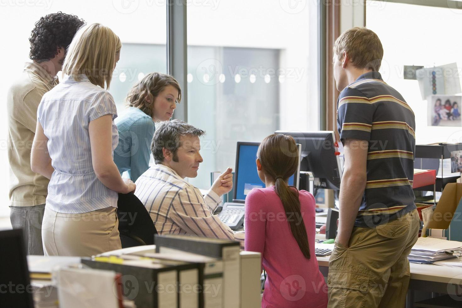 ejecutivos multiétnicos alrededor de un colega usando una computadora foto