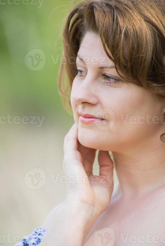 middle-aged woman in the summer park photo