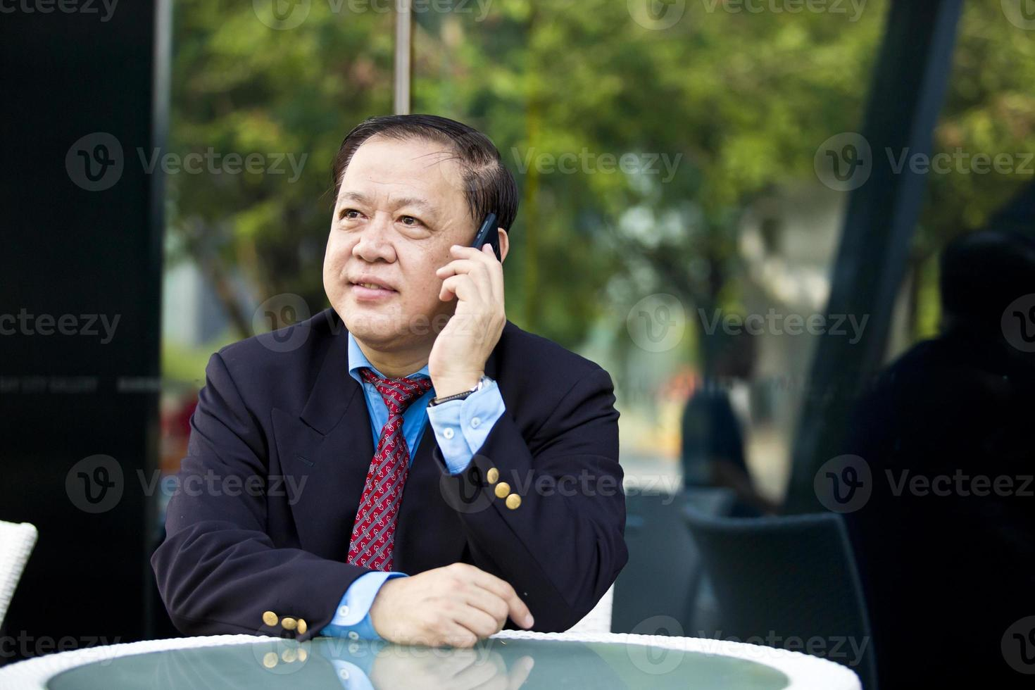 Asian businessman talking on smart phone photo