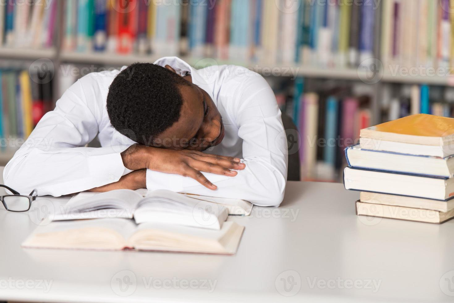 Tired Student Sleeping In Library photo