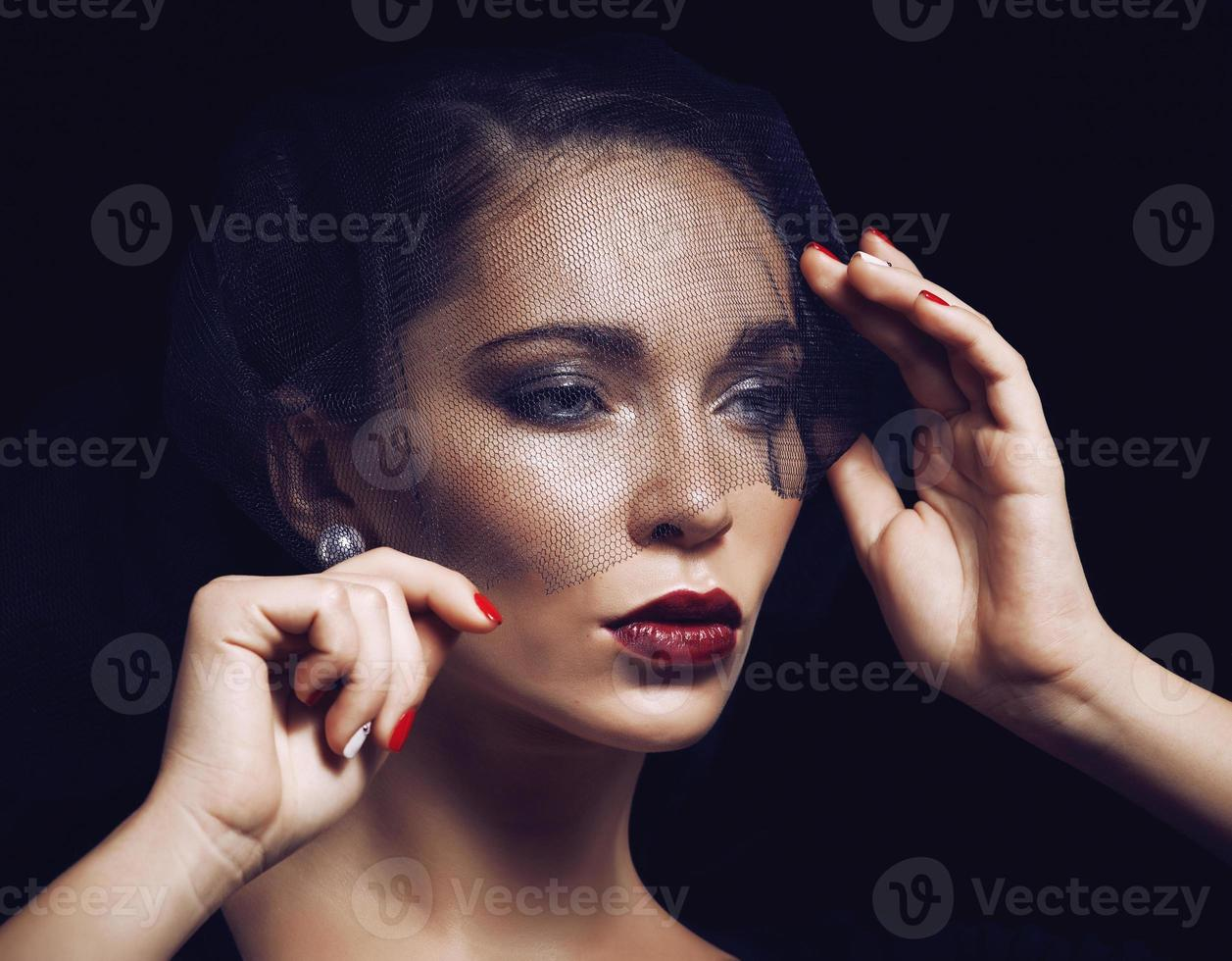 beauty brunette woman under black veil with red manicure close photo