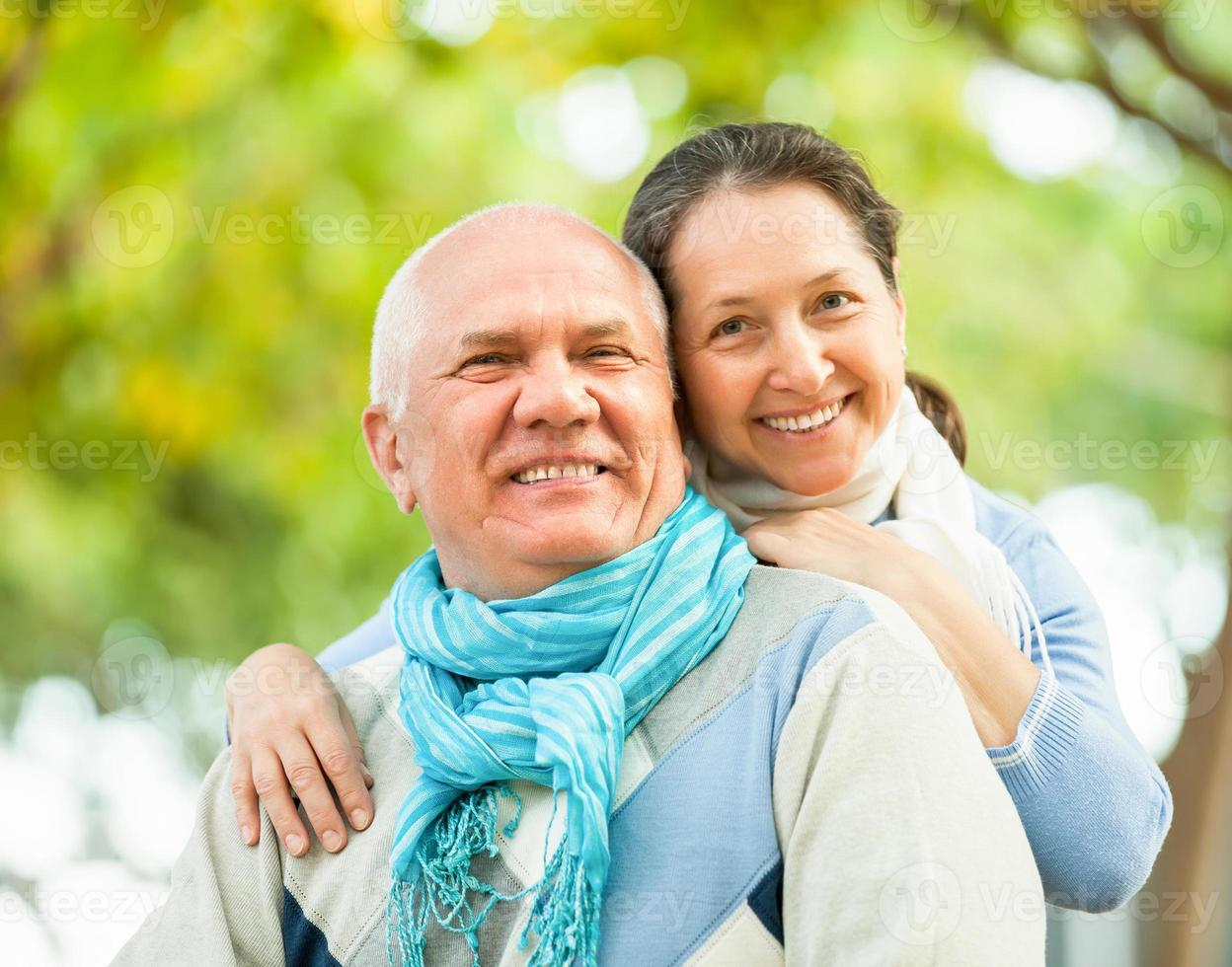 Happy senior man and mature woman against forest photo