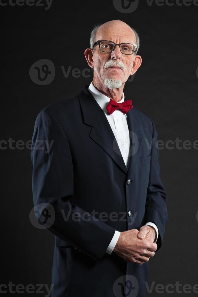 Senior hombre vestido con traje y corbata roja. Foto de estudio