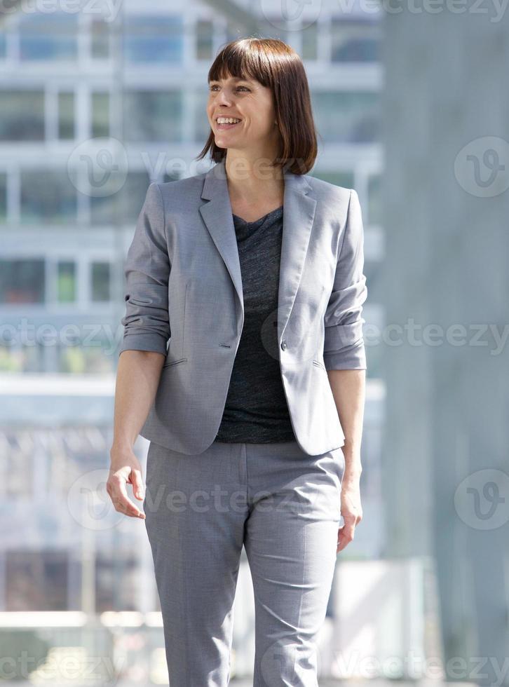 mujer de negocios caminando y sonriendo en la ciudad foto