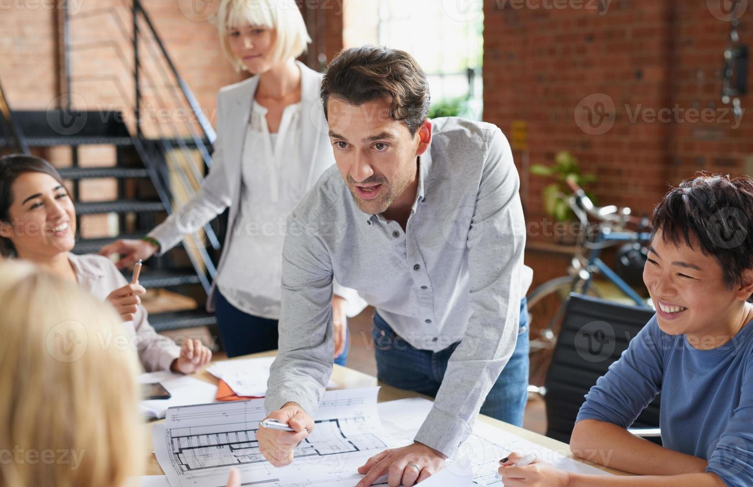 arquitectos trabajando en planes en la mesa de juntas de negocios foto