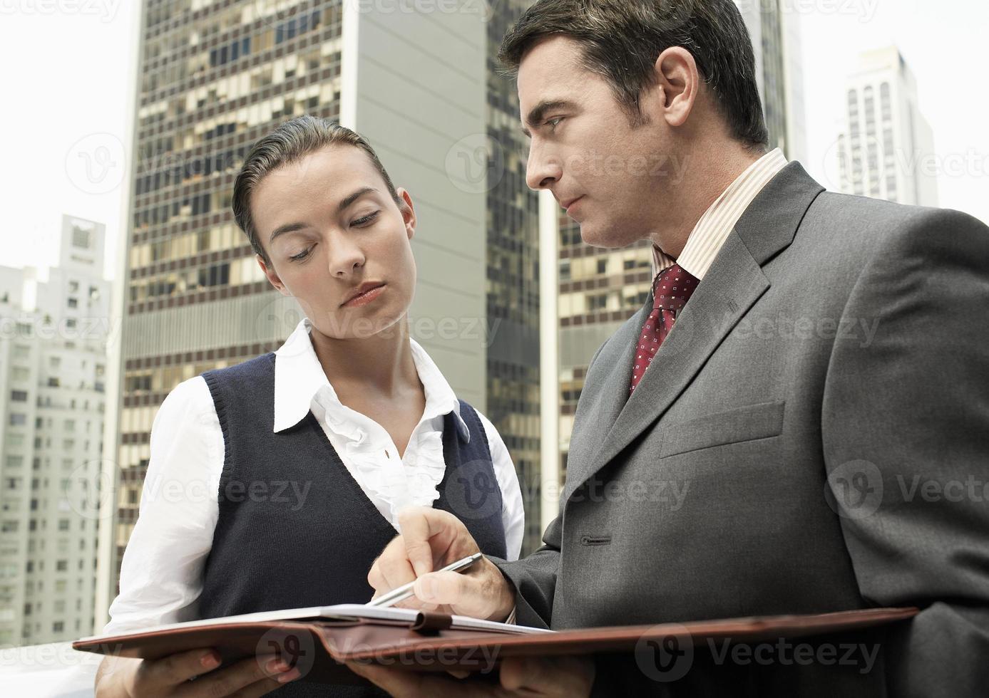 empresario mostrando papeleo a mujer al aire libre foto
