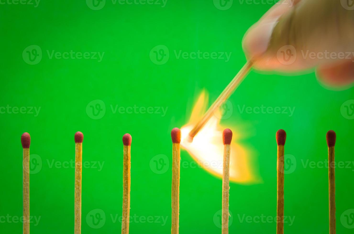 burnning match setting on green background for ideas and inspiration photo