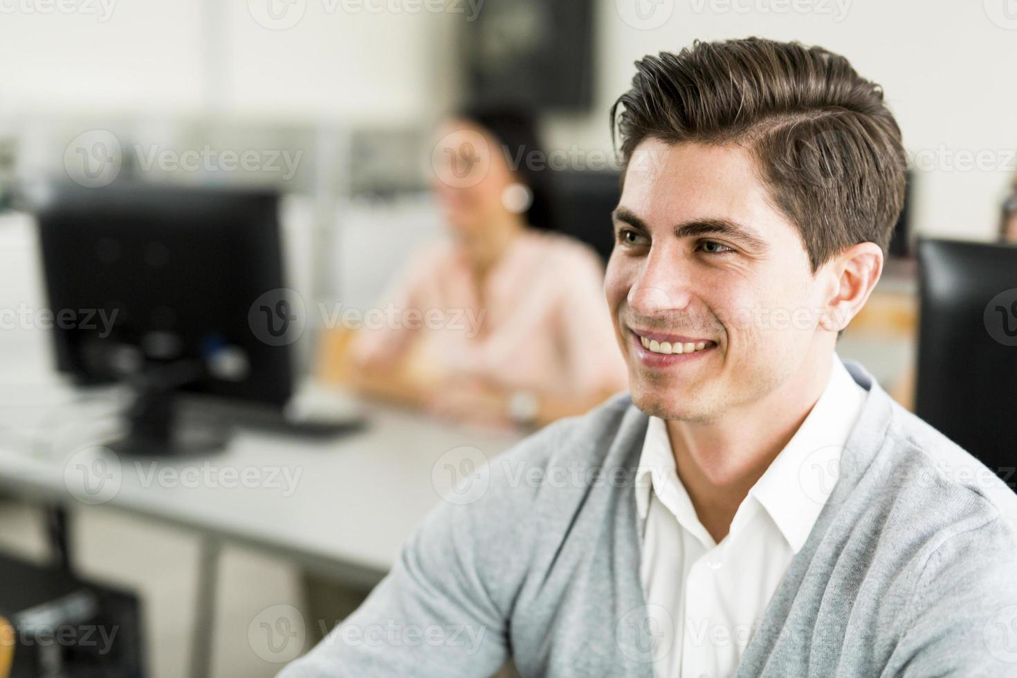 joven guapo estudiando tecnología de la información en un aula foto