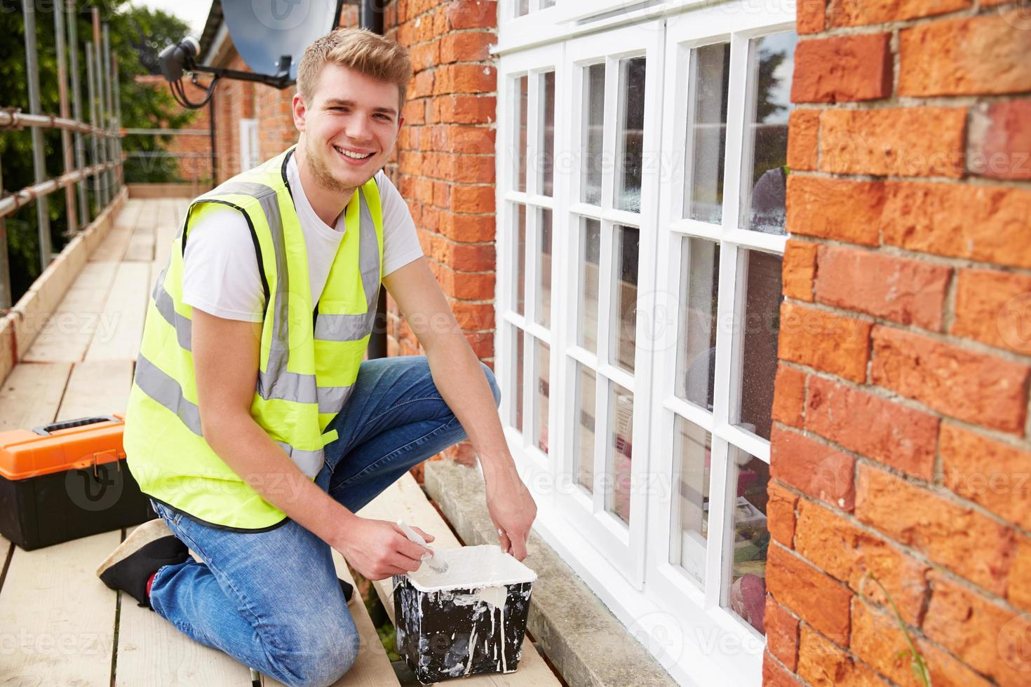 Portrait Of Decorator On Scaffolding Painting House Windows photo