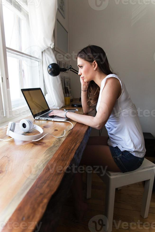 Young brunette working at her home on laptop. photo