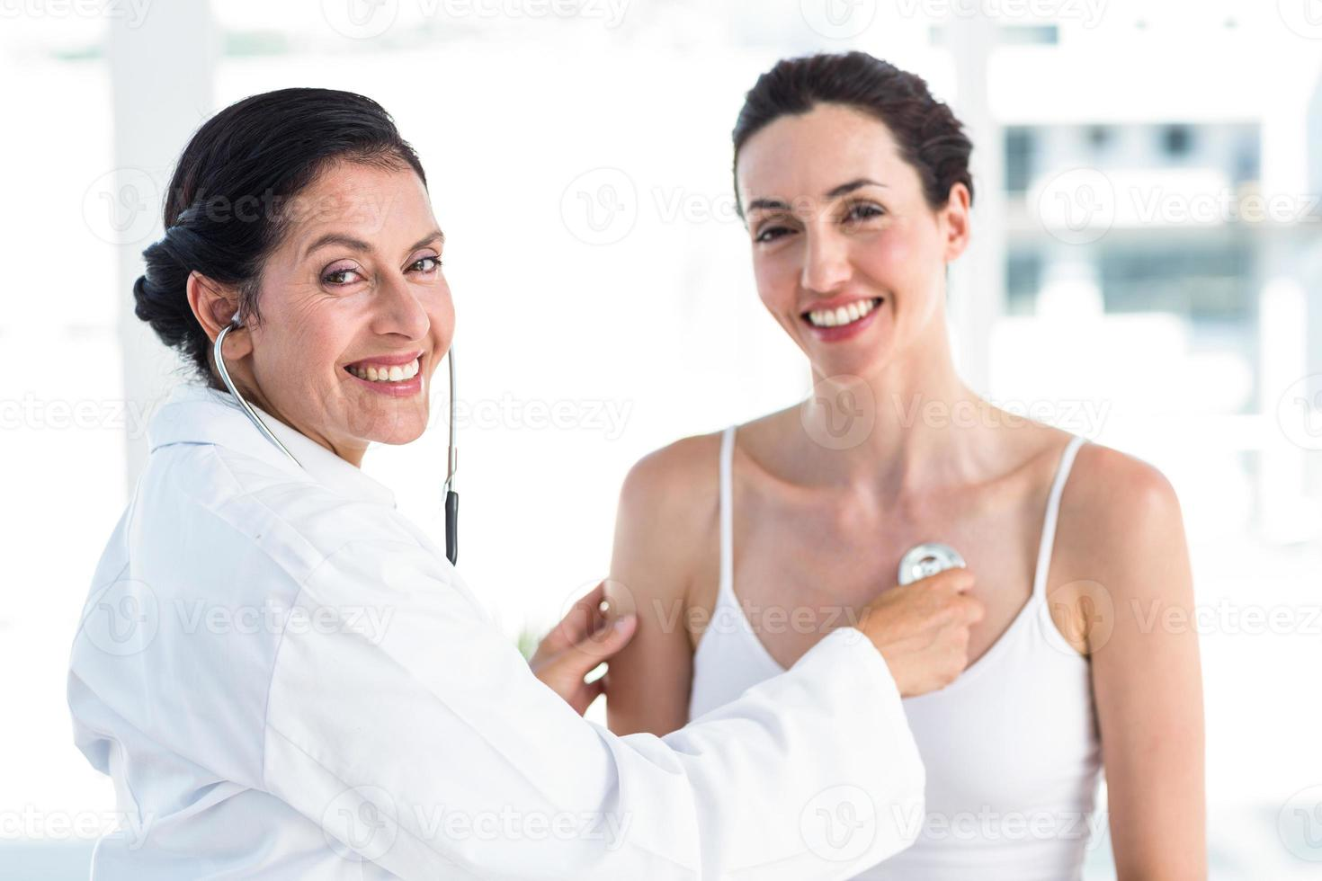 Doctor listening to patients chest with stethoscope photo