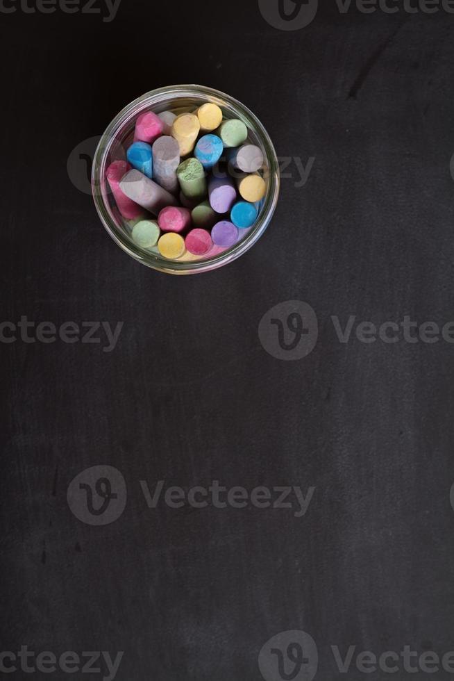Sobrecarga de pizarra y tarro de tiza de colores foto