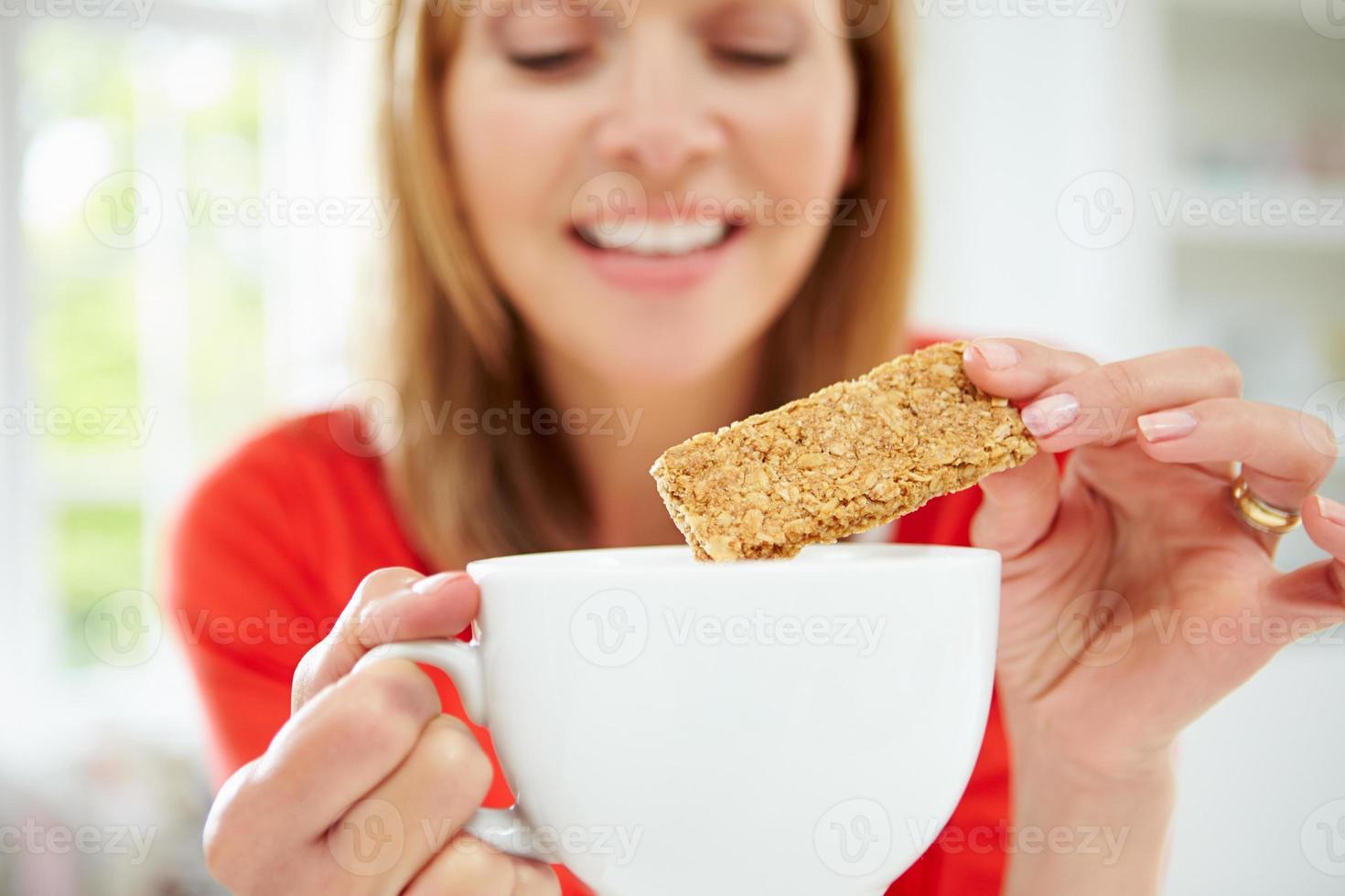Mujer mojando galletas en bebida caliente en casa foto