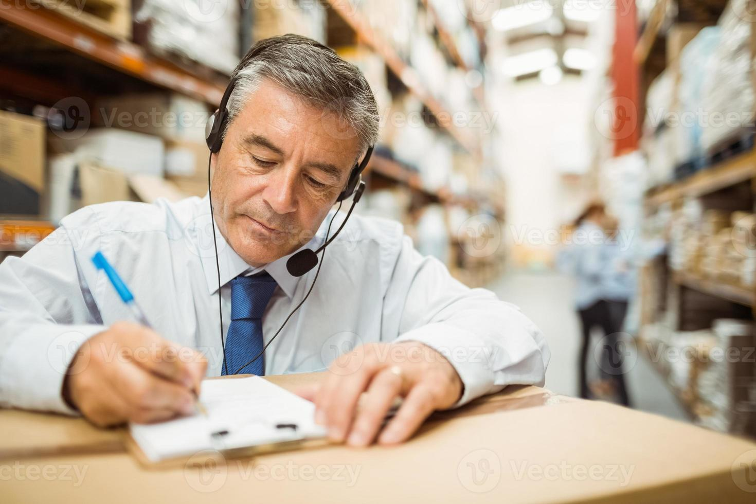 Warehouse manager writing on clipboard photo