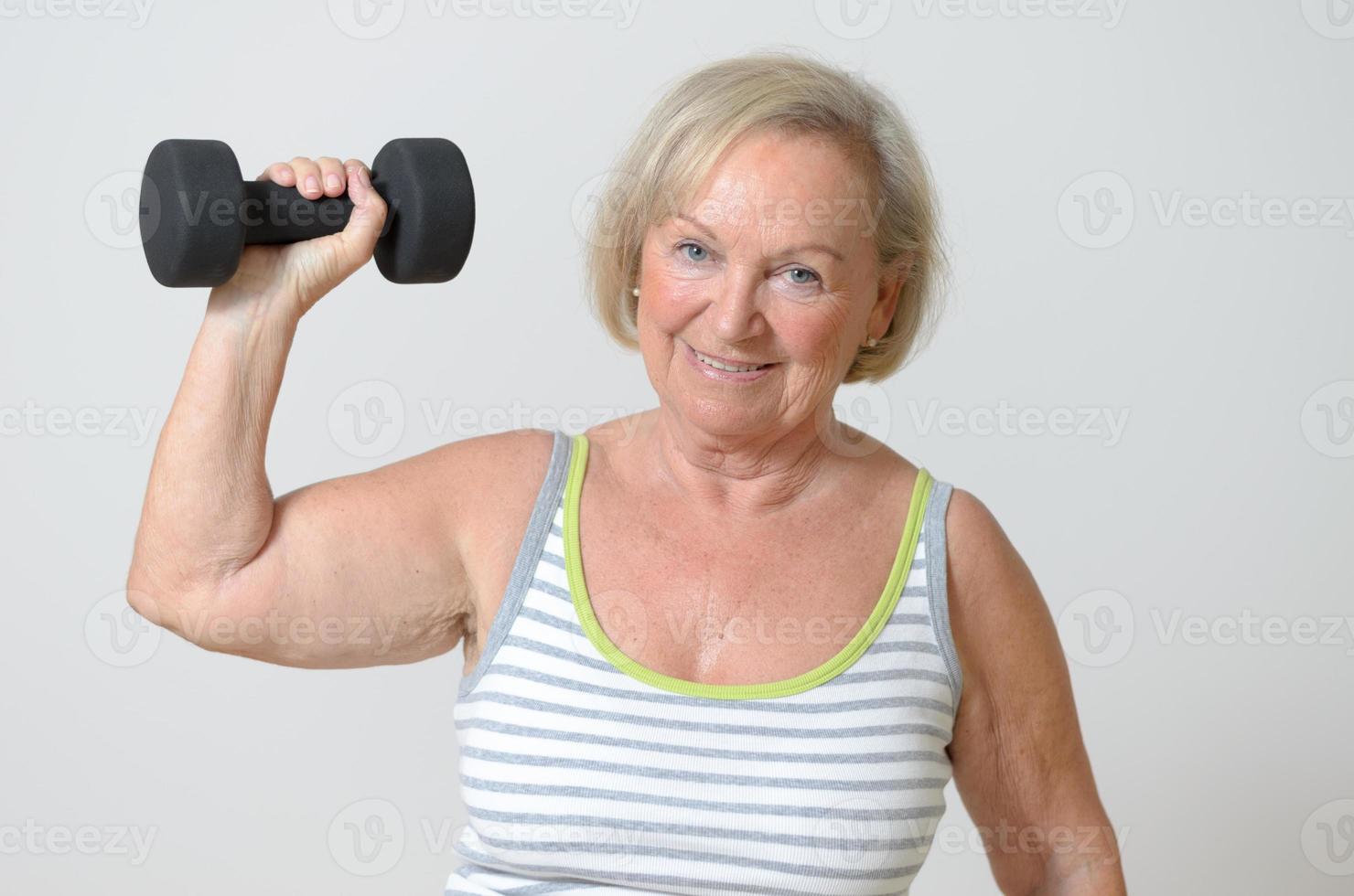 Señora mayor sosteniendo una pesa foto