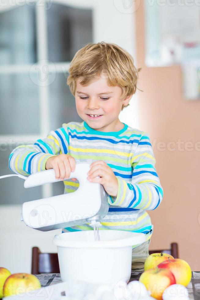 Chico rubio chico divertido hornear tarta de manzana en el interior foto