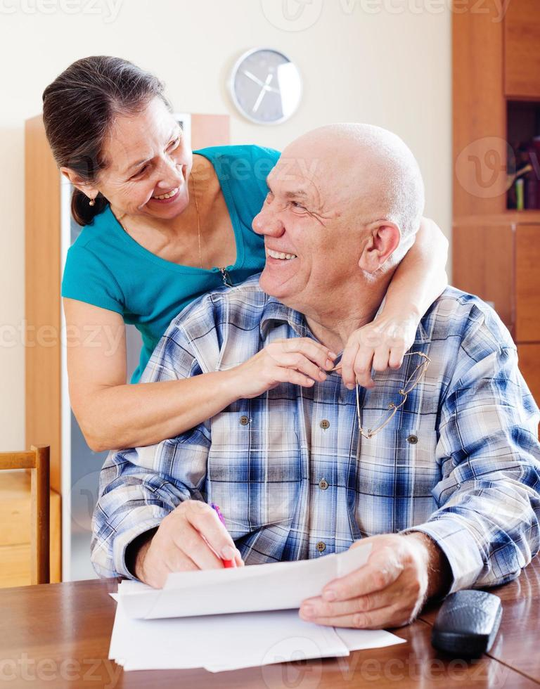 Happy  mature couple fills in paper photo