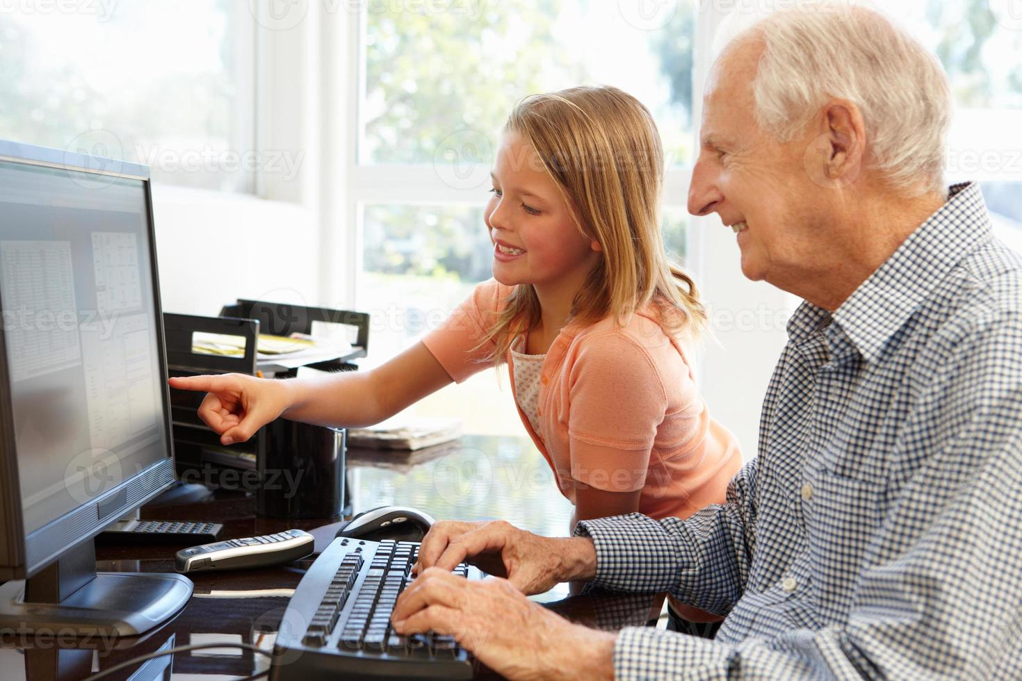 Senior man and granddaughter using computer photo
