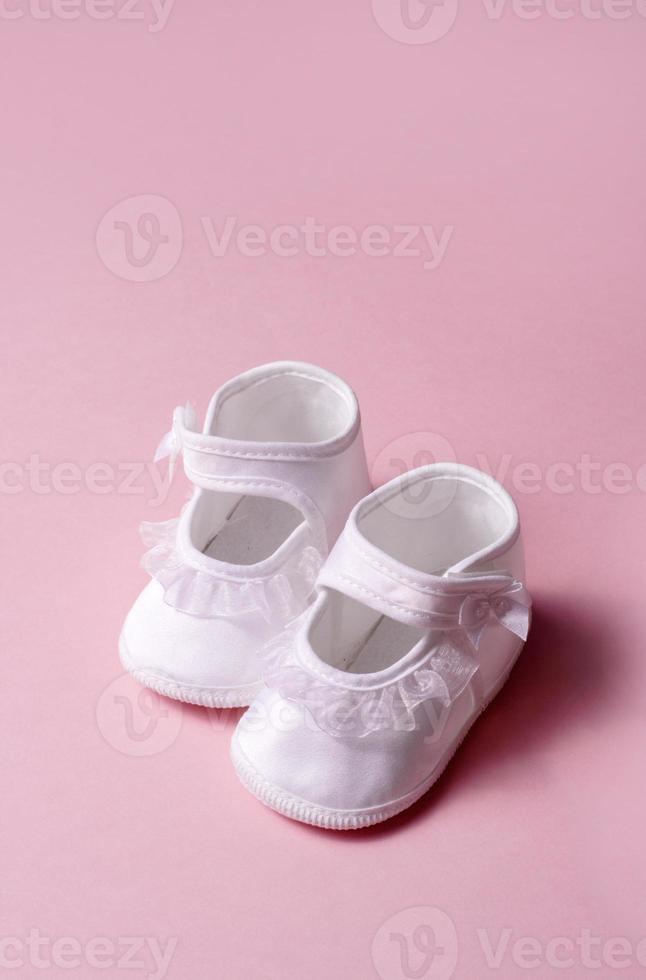 Girl's satin newborn baby shoes on a pink background photo