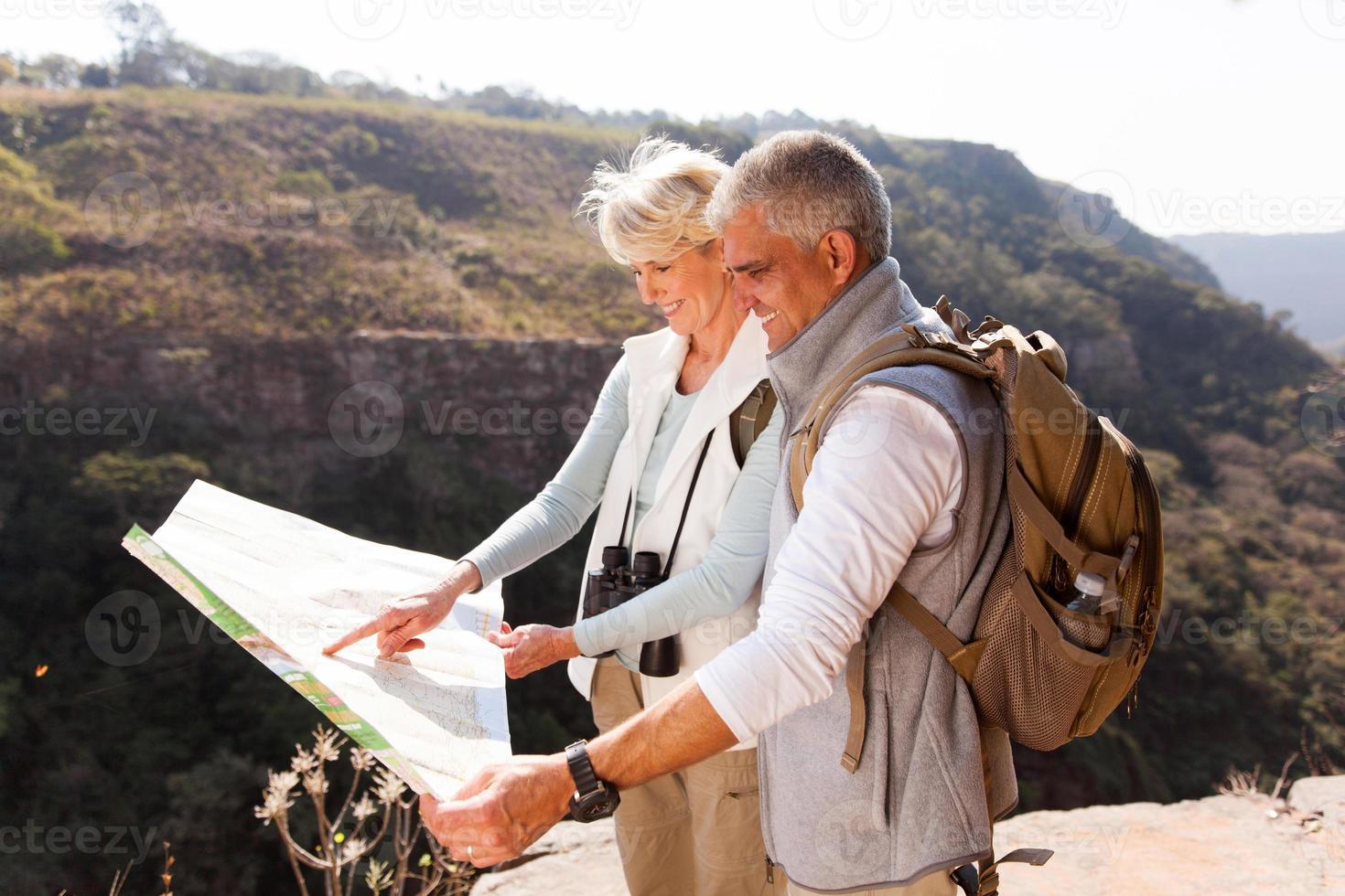 excursionistas de mediana edad mirando un mapa foto