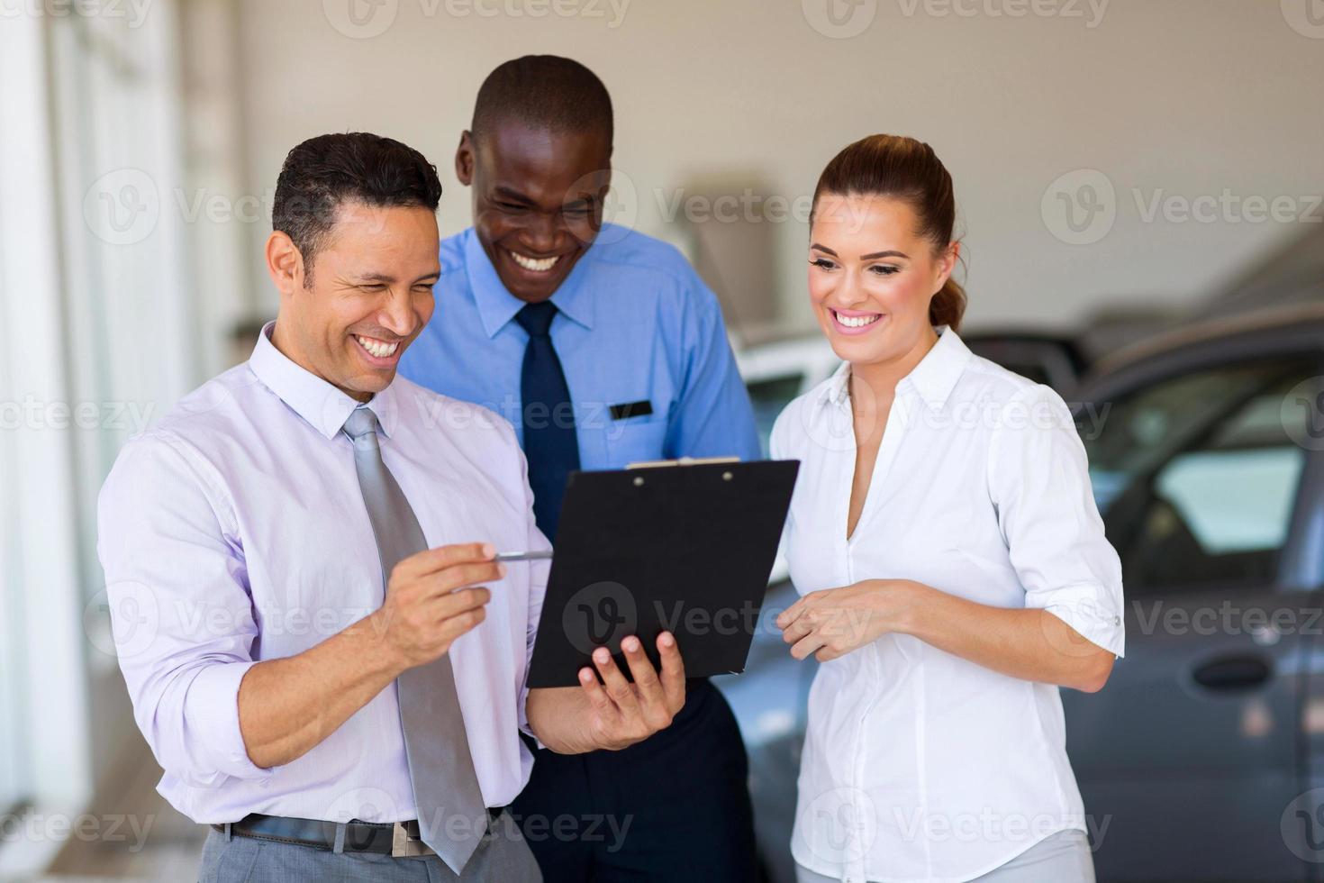 Grupo de consultores de ventas de automóviles que trabajan dentro de la sala de exposición de vehículos foto