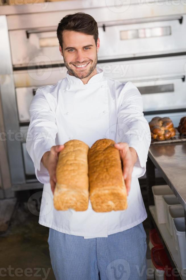 panadero sonriente mostrando hogazas de pan foto