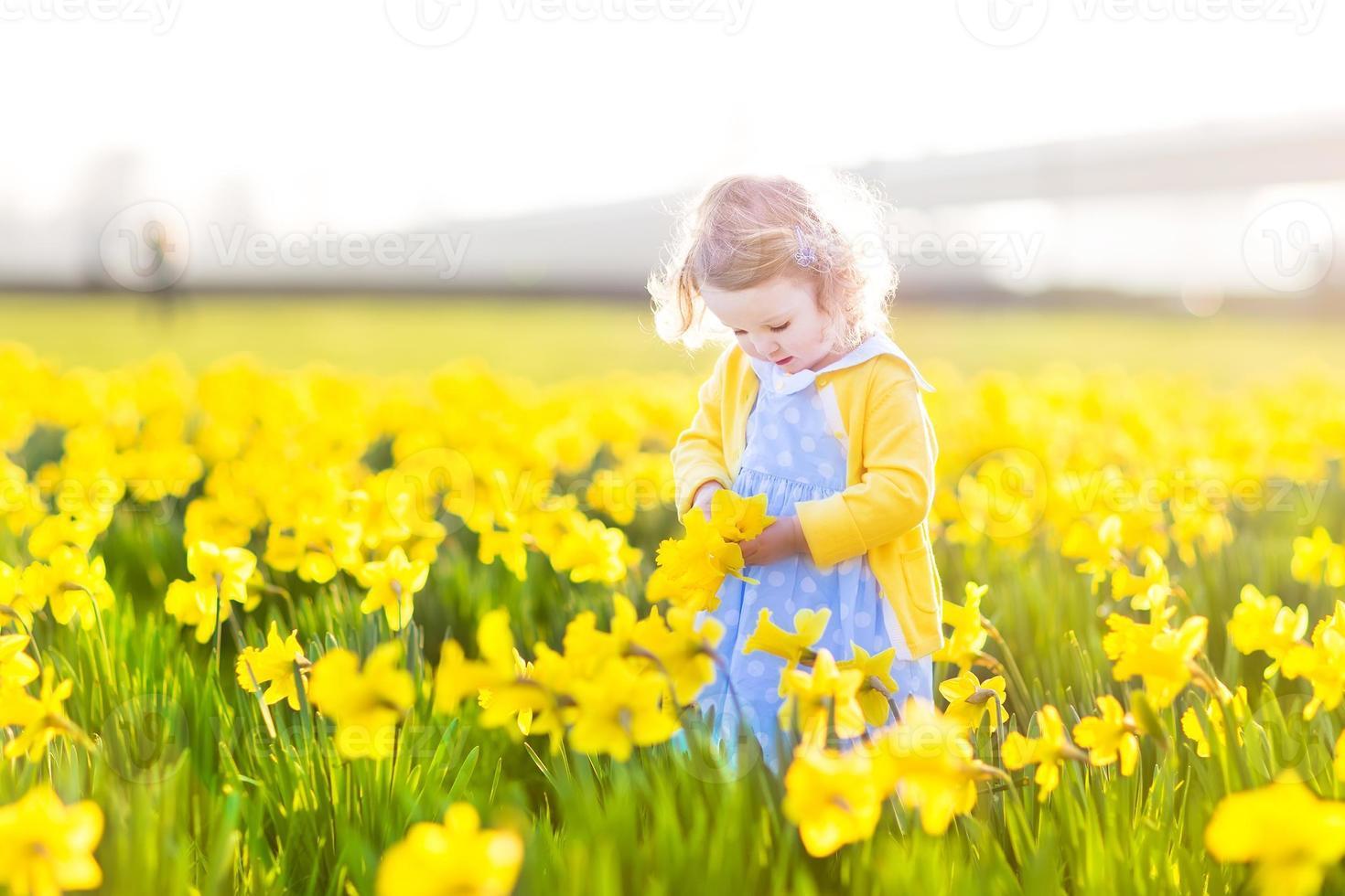 linda niña pequeña en vestido azul jugando en el campo de flores foto