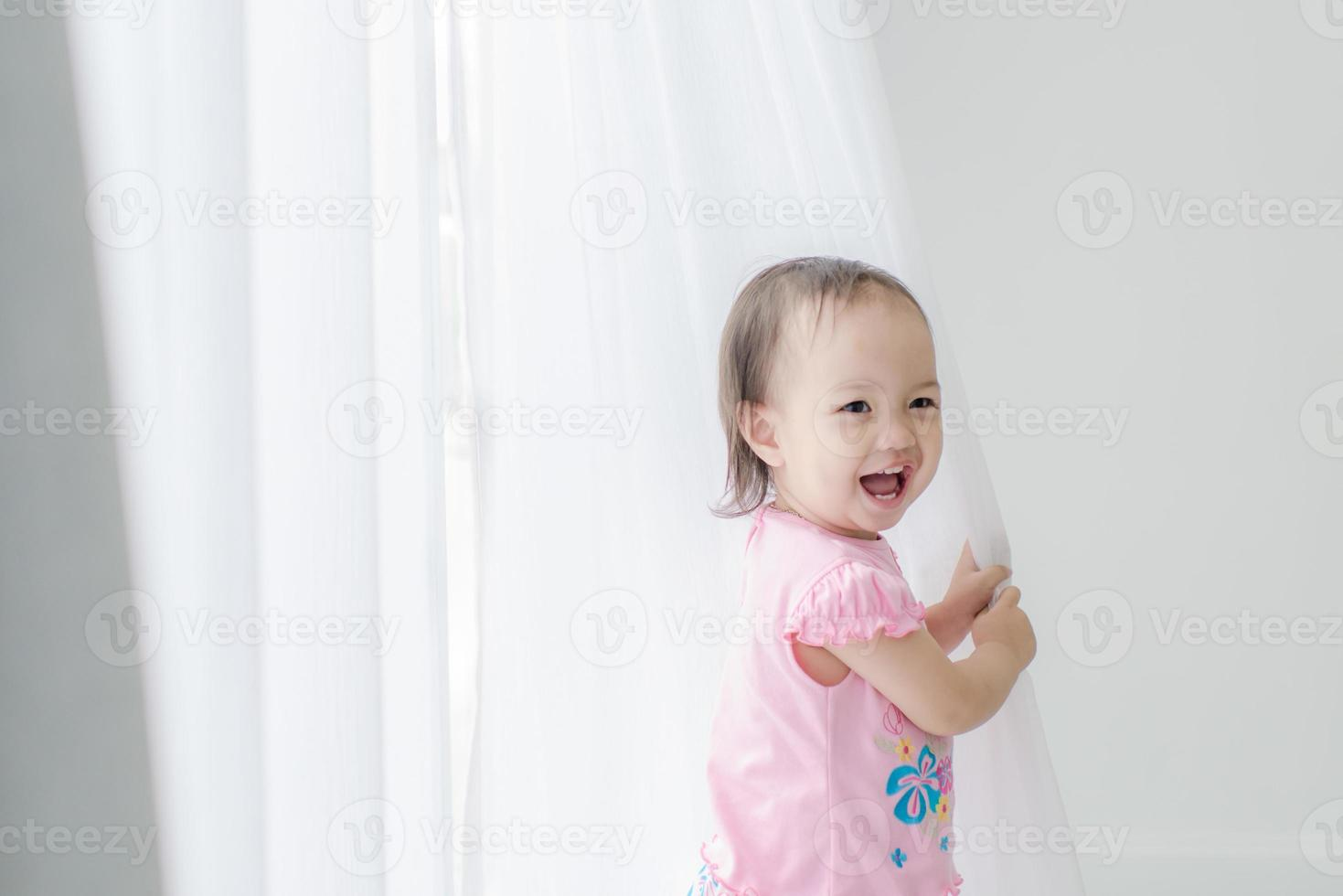 Asian girl holding white curtain at home. photo
