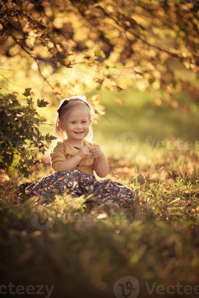 Adorable niña sonriente niña sentada en el parque foto