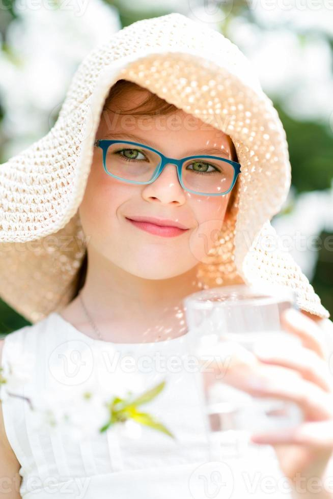 Summer little girl in straw hat drinking water outdoor portrait. photo