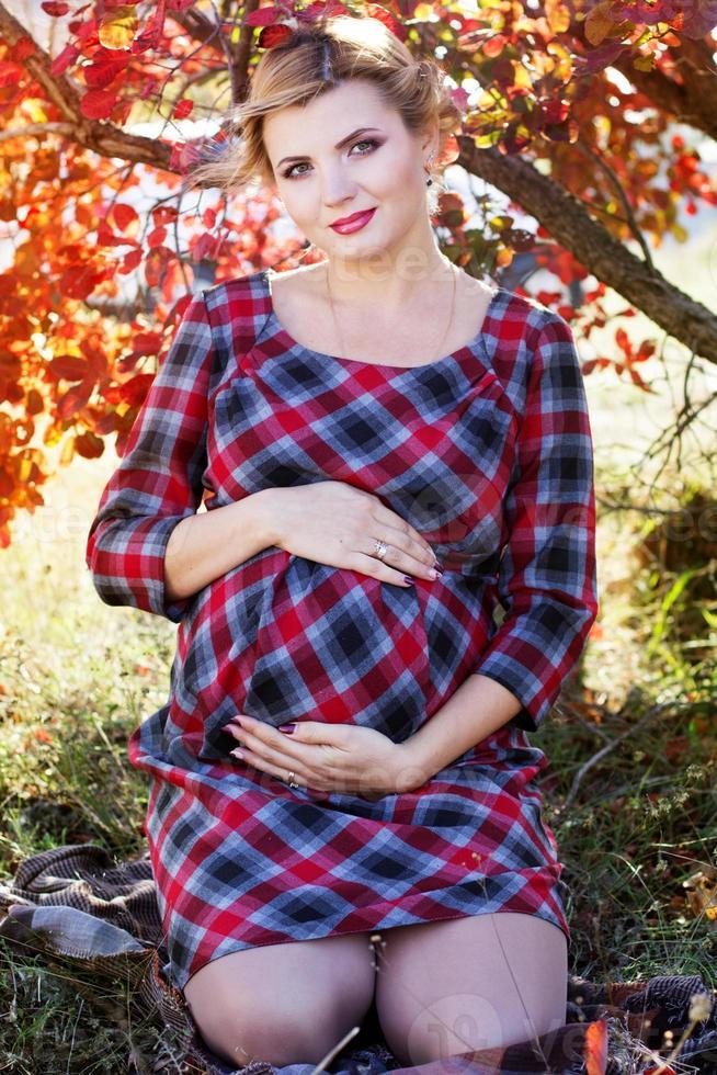 niña embarazada lleva vestido a cuadros en el parque foto