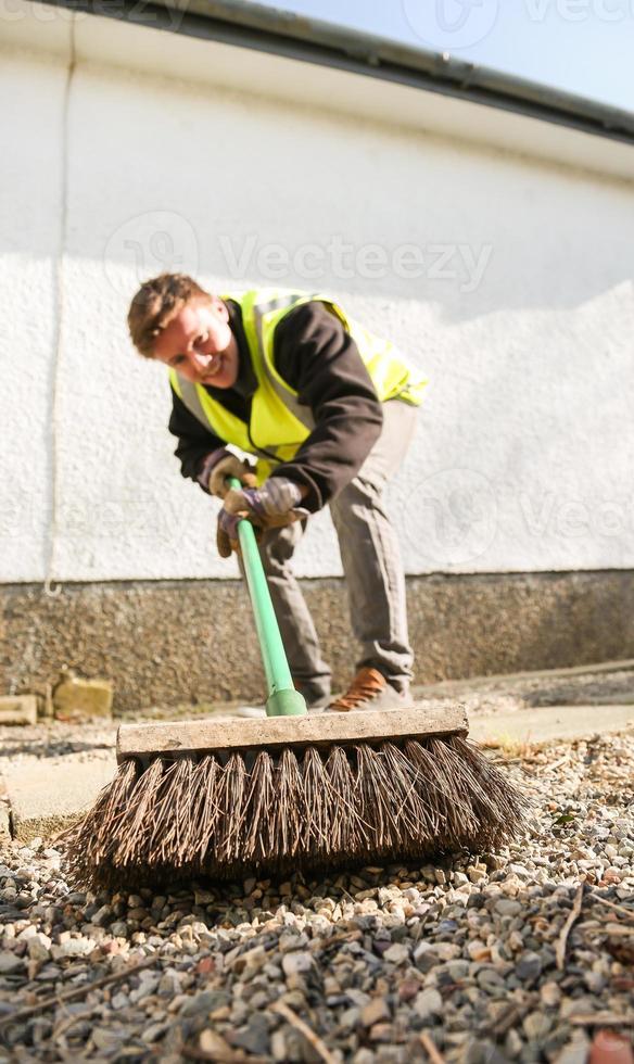joven trabajador manual barre un camino foto