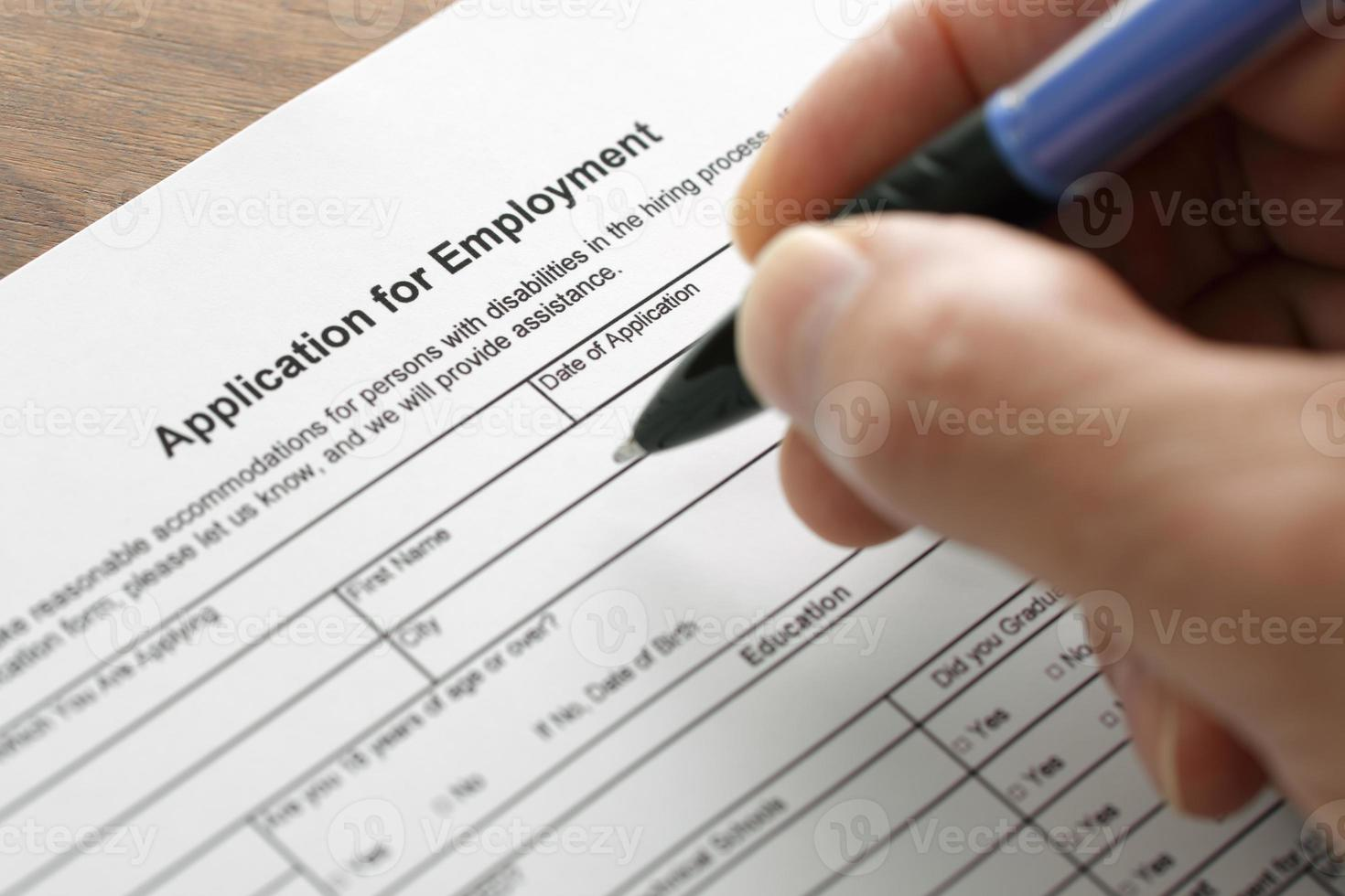 Close-up of a hand filling out a job application photo