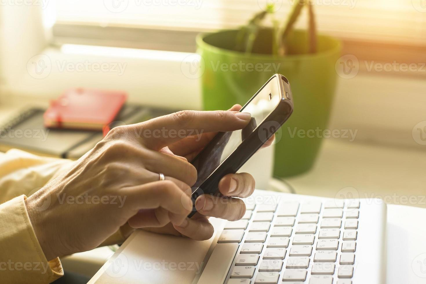 Mujer con teléfono móvil, teclado de computadora en el fondo. foto