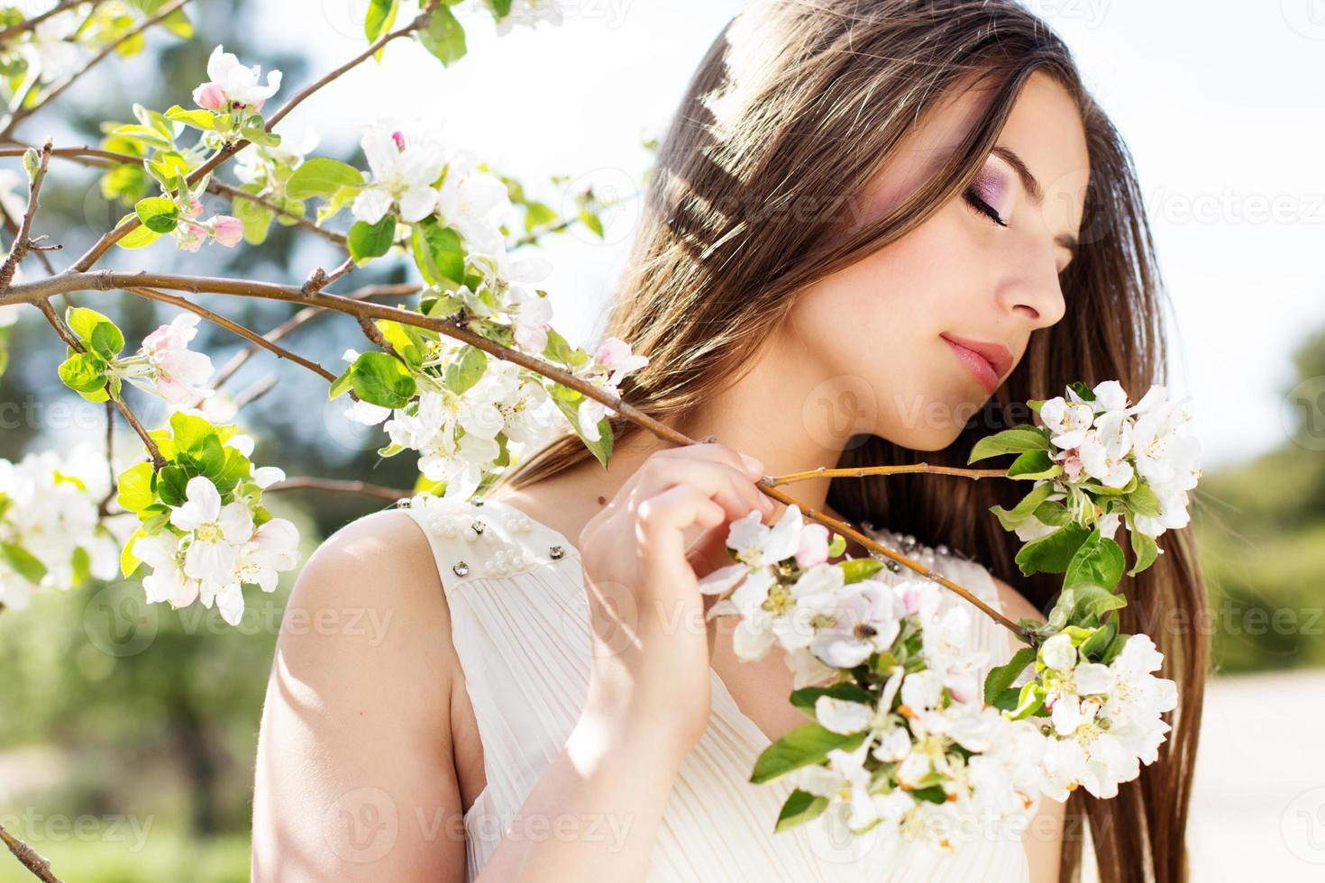 hermosa niña en un jardín de cerezos en flor foto