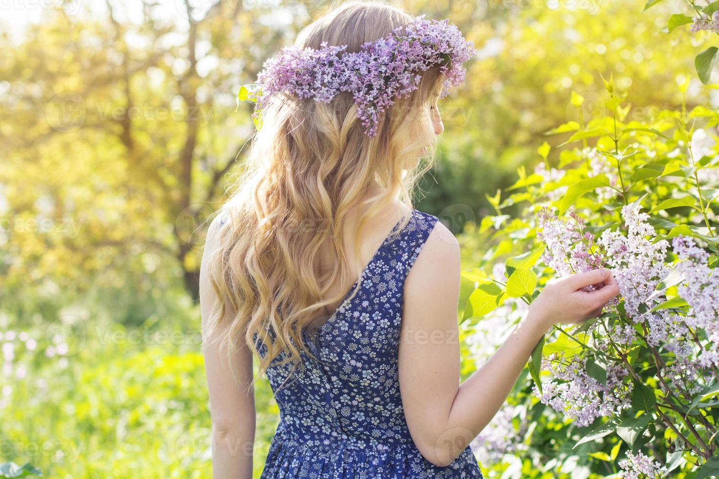 Chica con corona de flores lilas en parque verde foto
