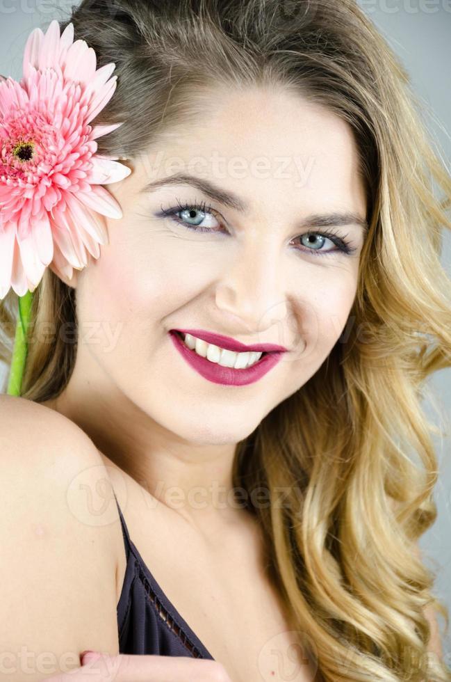 niña con una hermosa sonrisa flor de levadura en las manos foto