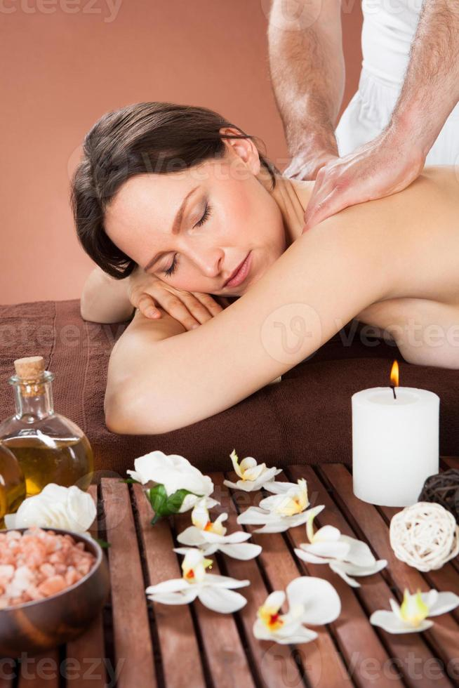 Woman Receiving Back Massaging In Spa photo