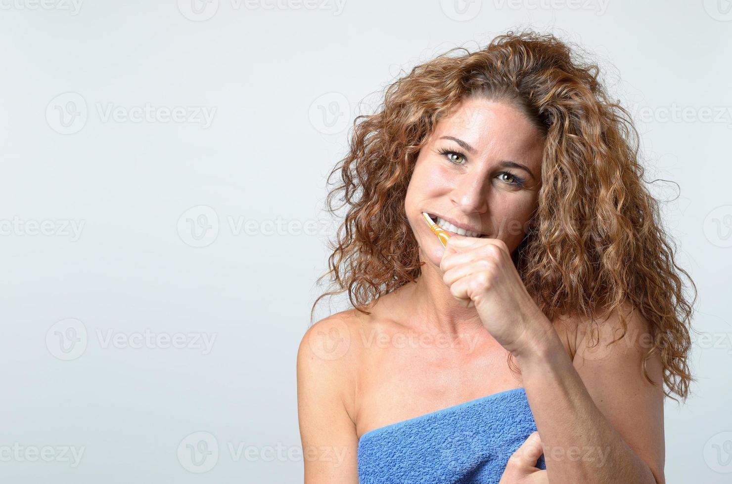 mujer limpiando sus dientes con un cepillo de dientes foto