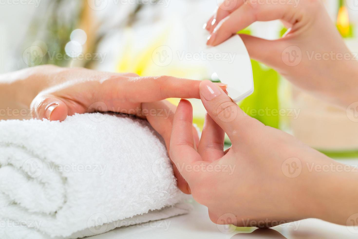 Woman in nail salon receiving manicure photo