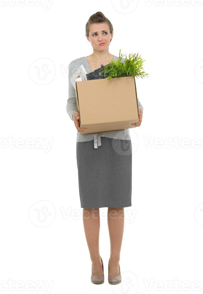 concerned woman employee holding box with personal items photo