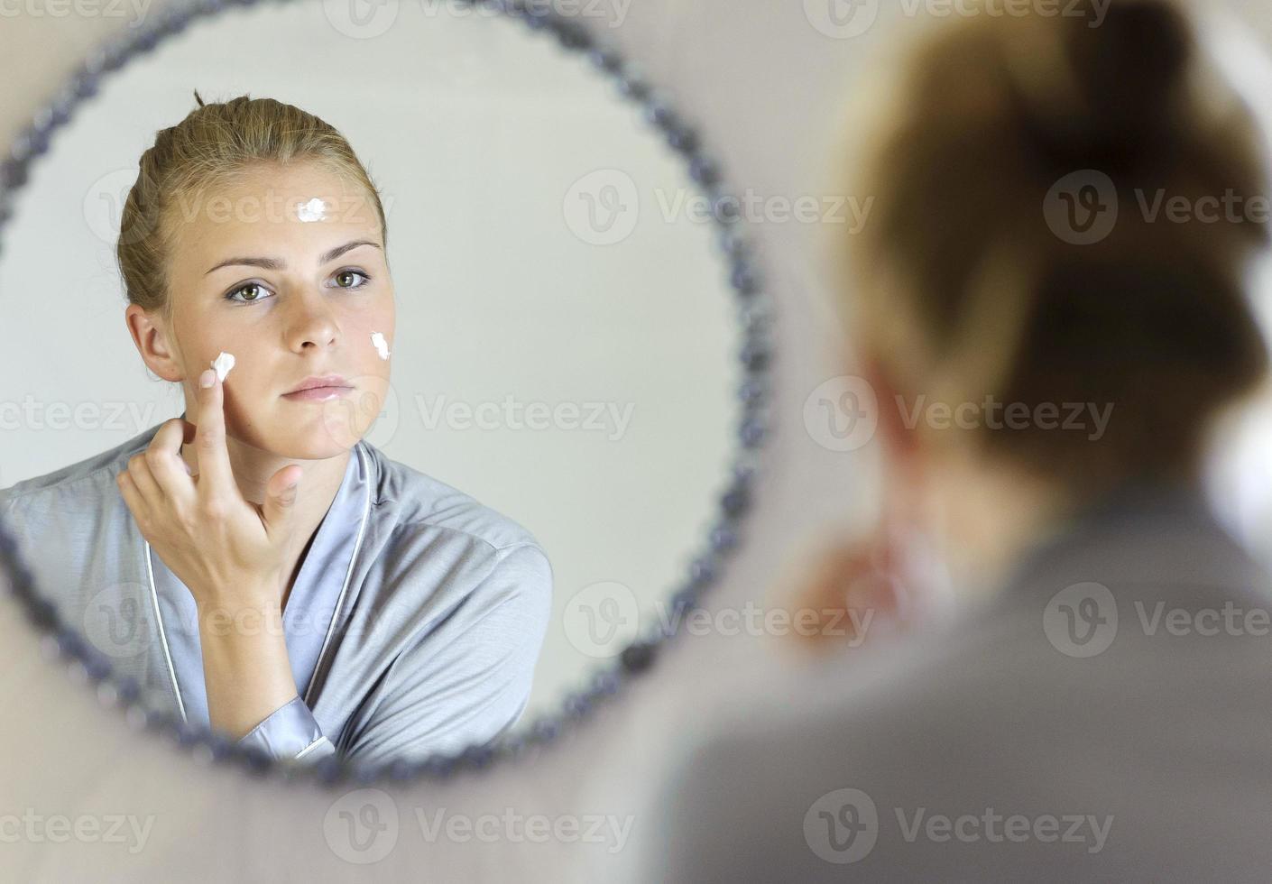 Beautiful young woman applying face cream photo