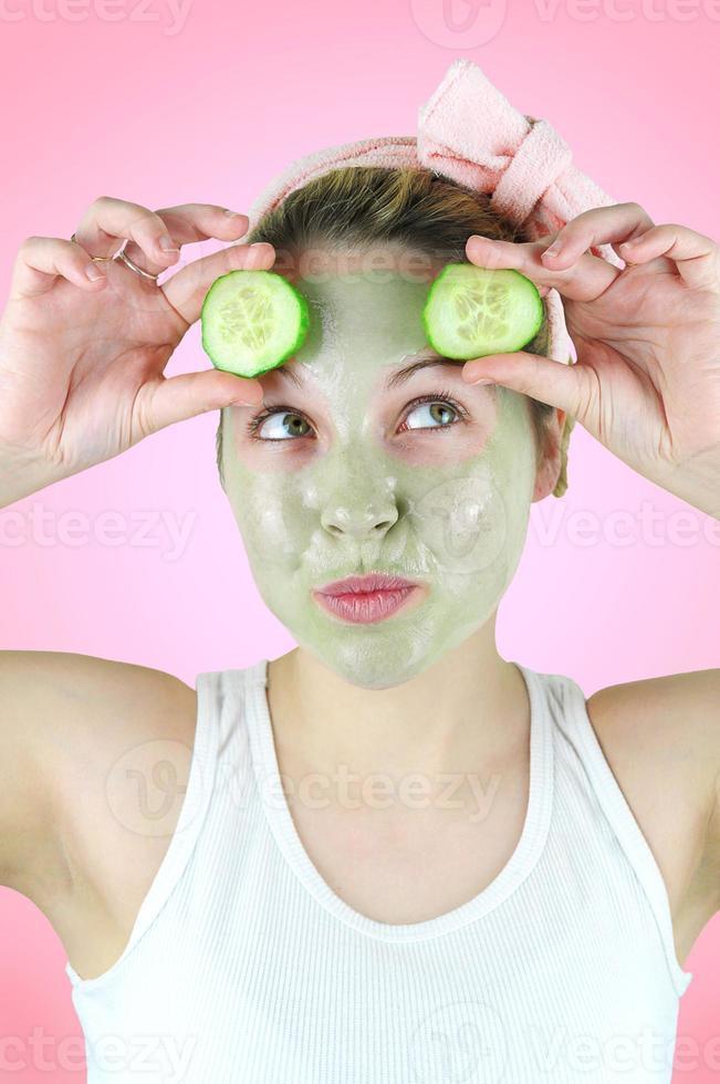Mujer divertida con una máscara facial verde y pepinos. foto