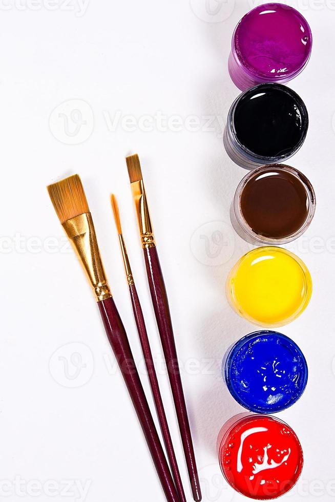 Bottles with gouache paints and different kinds of brushes. photo