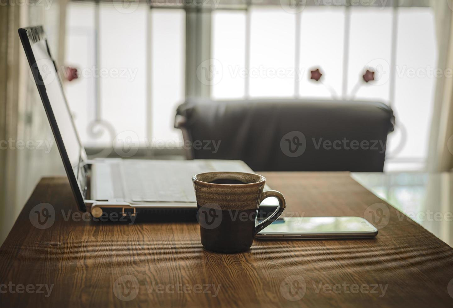 Business work place with cup of coffee smartphone and laptop. photo
