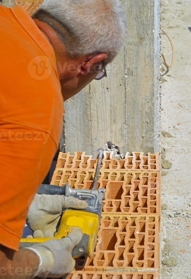 Mason drills a hole with a power drill photo