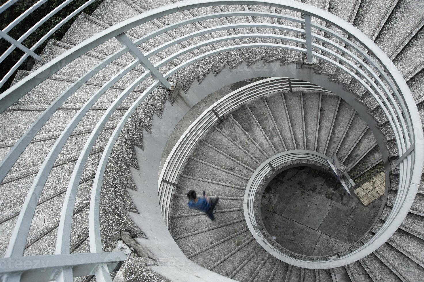 hombre en una camisa azul bajando una escalera de caracol foto
