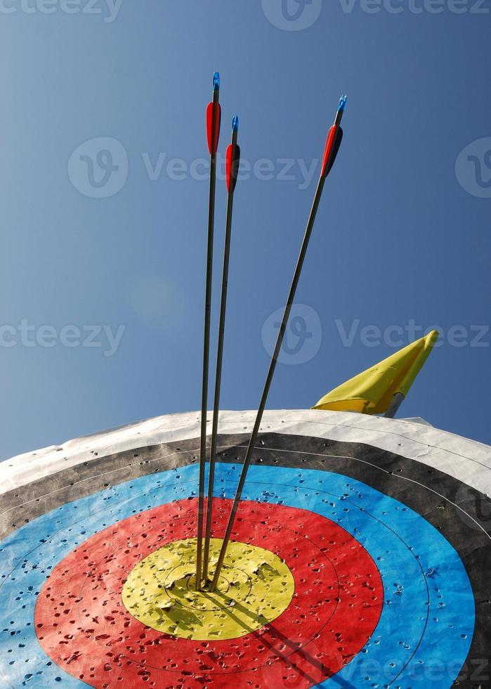 Tres flechas que sobresalen de una diana amarilla foto