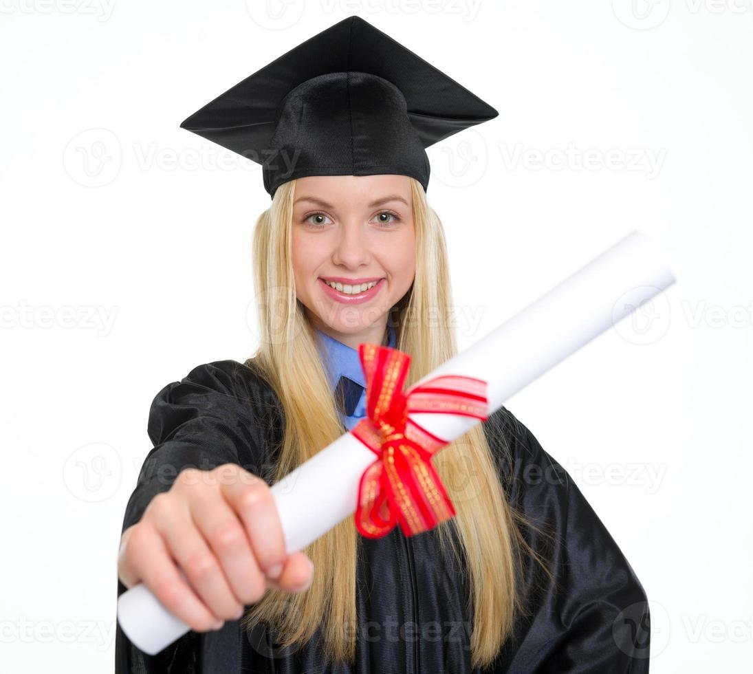 sonriente mujer joven en toga de graduación mostrando diploma foto